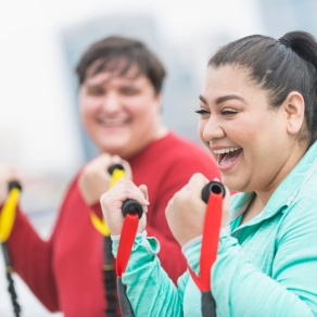 Hispanic woman, friend exercising with resistance bands
