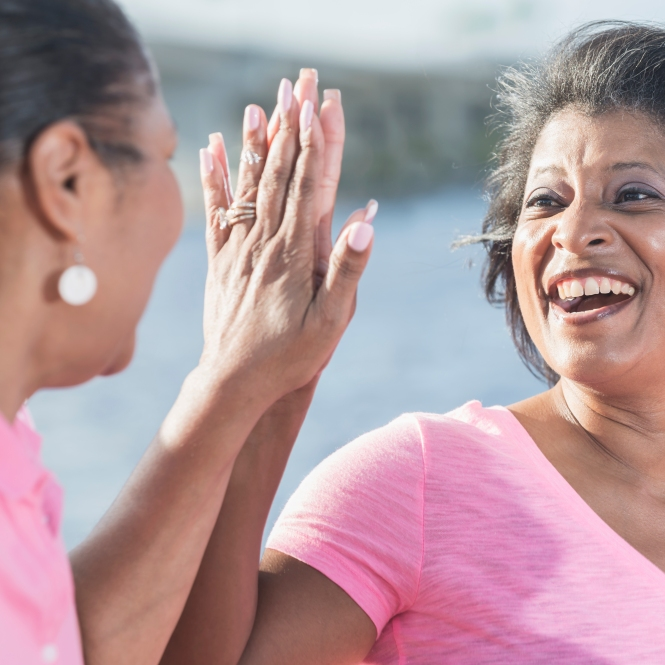 Two mature African American woman in pink, high fives