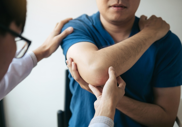 Physical therapists are checking patients elbows at the clinic office room.