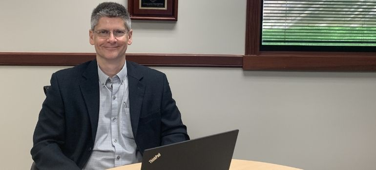 Kettering Health Stroke Medical Director Timothy Schoonover at table with laptop