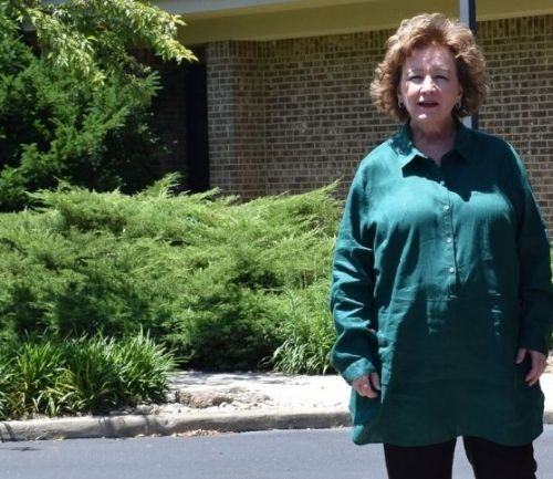 Lisa LePage stands in front of Clearkcreek Chapel bushes