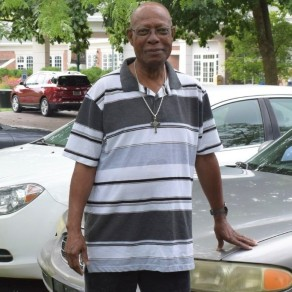 Patient Darryl stands in the parking lot, touching his car