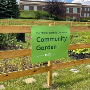 Community garden sign with plants in background.