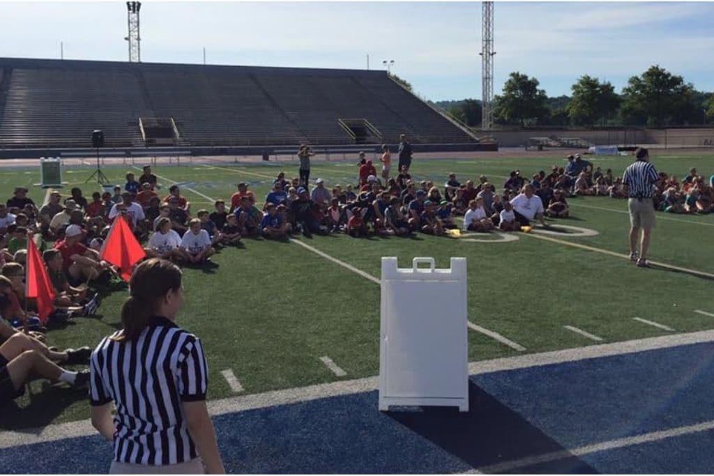 Students sit on football field