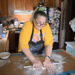 Woman rolls out dough by hand