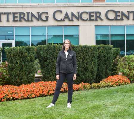 Beth stands in front of Kettering Cancer Center sign