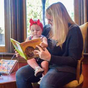 Woman reads a book to a baby sitting on her lap