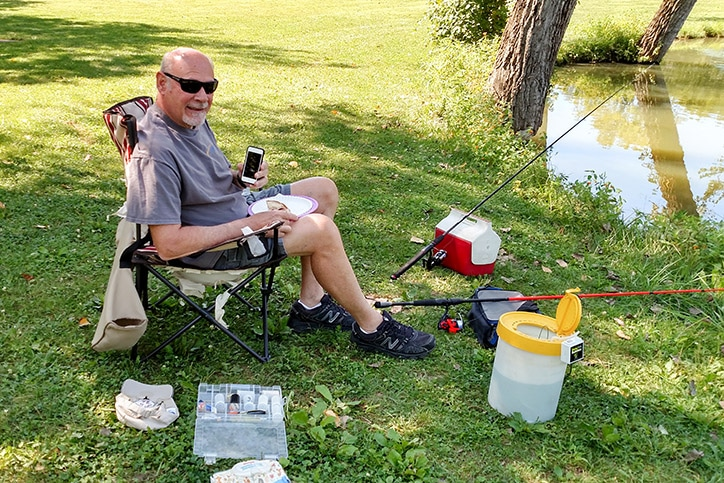 Don sits by water preparing to fish with iPod in hand